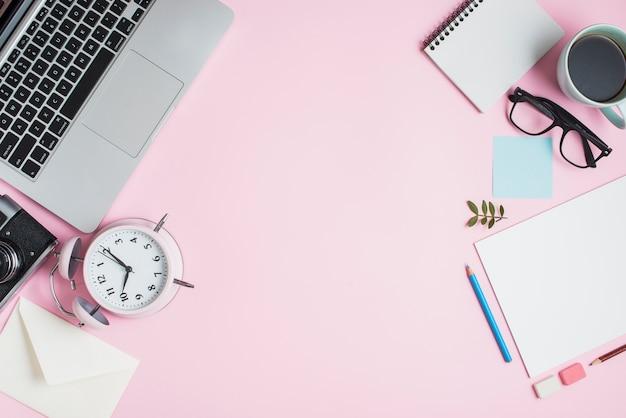 Schreibwaren; laptop; kamera; briefumschlag; wecker und schreibwaren auf rosa hintergrund Kostenlose Fotos