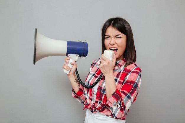 Schreiende junge asiatische frau, die lautsprecher hält. Kostenlose Fotos