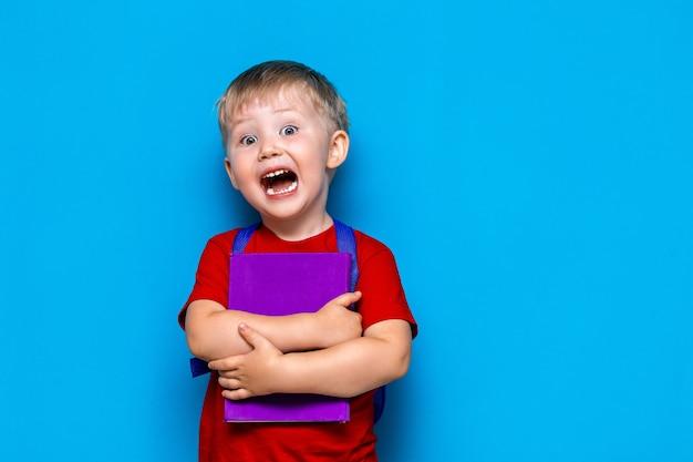 Schreiender junge mit buch und schultasche, verärgert überrascht und ängstlich vor der schule. zurück zur schule Premium Fotos