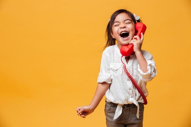 Schreiendes aufgeregtes kind des kleinen mädchens, das durch rotes retro- telefon spricht. Kostenlose Fotos