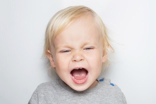 Schreiendes forderndes kaukasisches baby in einem grauen t-shirt auf weiß Premium Fotos