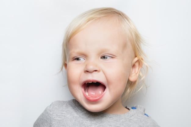 Schreiendes kaukasisches baby in einem grauen t-shirt auf dem weißen hintergrundporträt Premium Fotos