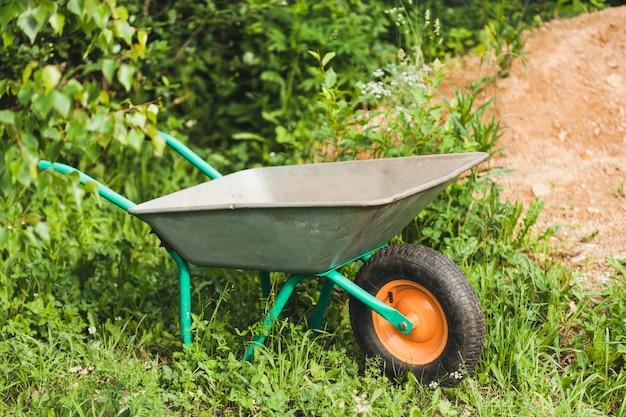 Schubkarre, wagen zum transport von land, material, gras und anderen dingen im garten, gartenarbeit, bau, feldarbeit, pflanzen, beeten Premium Fotos