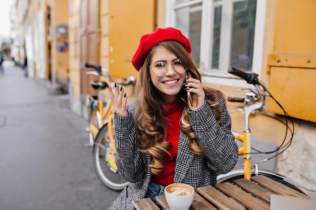 Schüchterne frau mit lockiger frisur, die im café im freien mit lächeln im septembertag aufwirft Kostenlose Fotos