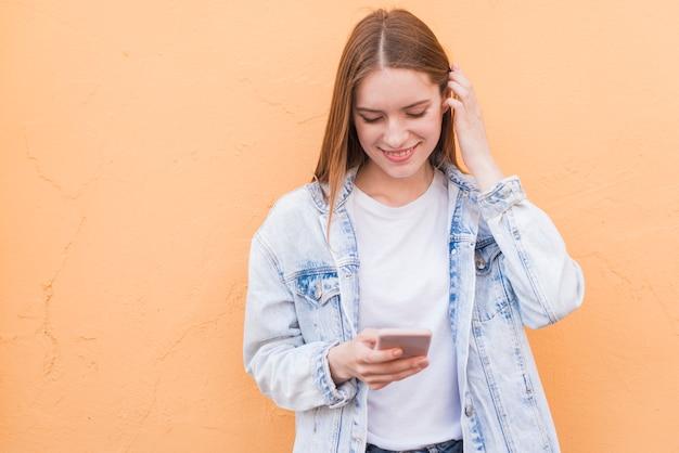Schüchterne lächelnde frau, die mobiltelefon über beige strukturierter wand verwendet Kostenlose Fotos