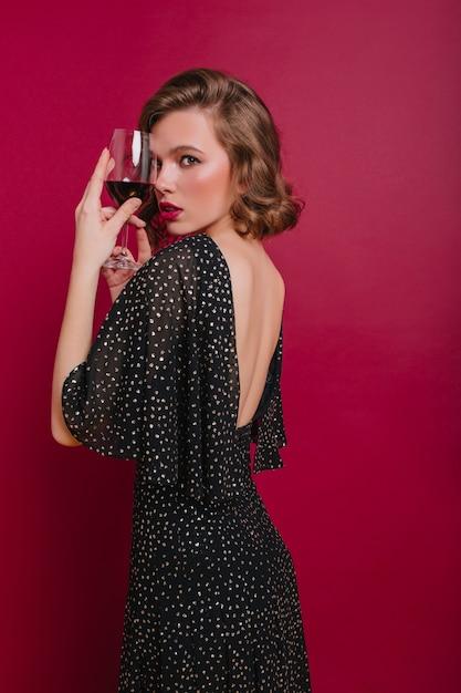 Schüchternes mädchen im trendigen partykleid, das über schulter steht auf dunklem hintergrund steht Kostenlose Fotos