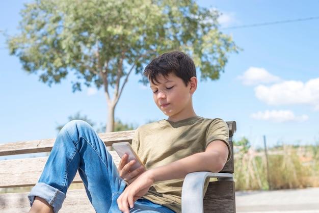 Schüler auf der bank, die pause unter verwendung des mobiles macht Premium Fotos