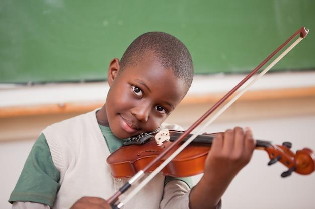 Schüler, der die violine spielt Premium Fotos