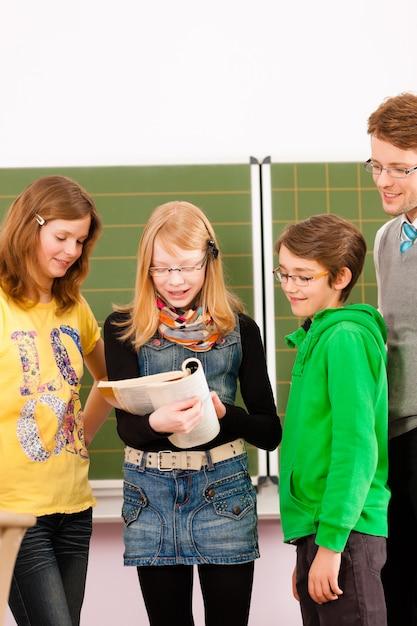 Schüler mit lehrer auf tafel in der schule Premium Fotos