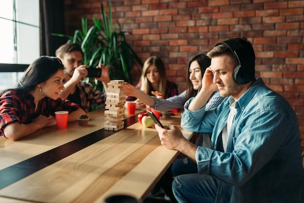 Schüler spielen jenga am tisch im café Premium Fotos