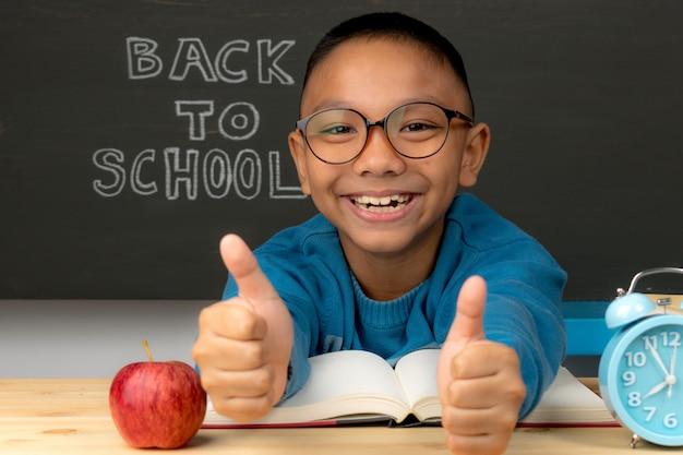 Schüler von der grundschule in brillen mit dem anheben der hand. kind ist bereit zu lernen. zurück zur schule. Premium Fotos