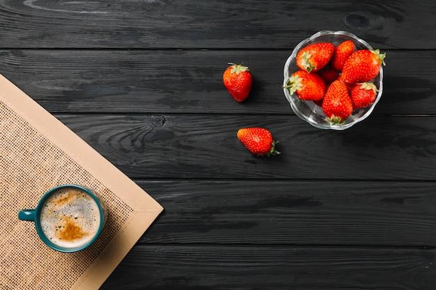 Schüssel der erdbeere und der kaffeetasse auf jutefaser placemat über schwarzer strukturierter oberfläche Kostenlose Fotos