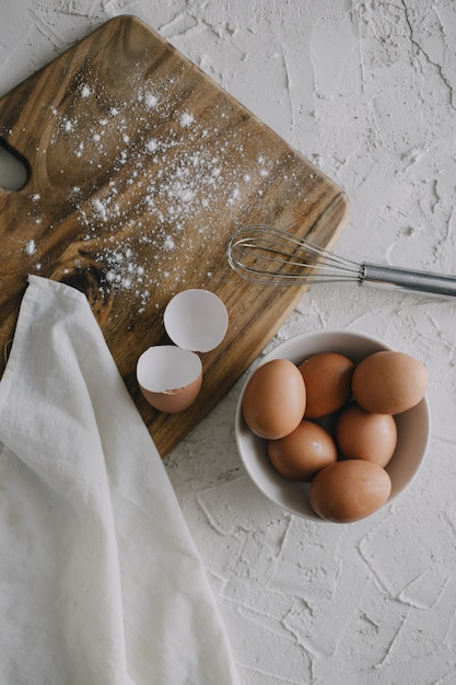 Schüssel eier und ein silberner schneebesen neben einem schneidebrett auf einer weißen oberfläche Kostenlose Fotos