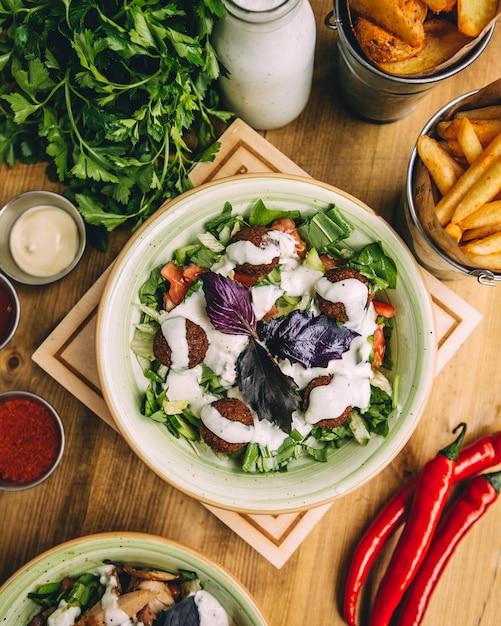 Schüssel fleischklöschensalat geschmückt mit jogurtsoße Kostenlose Fotos