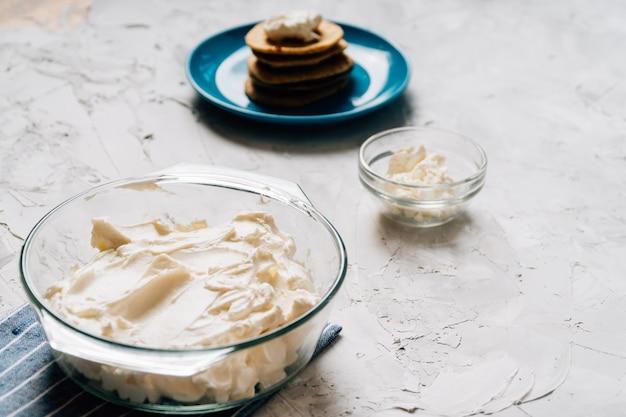 Schüssel frischkäse selbst gemacht in der glasplatte mit vertikalem gesundem lebensmittel der pfannkuchen und des hüttenkäses Premium Fotos