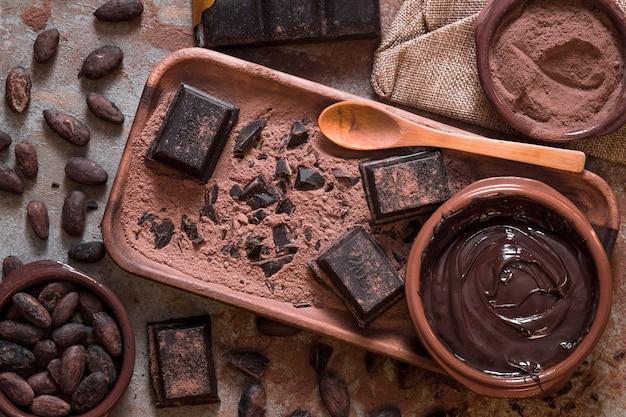 Schüssel geschmolzene und stücke schokolade mit kakaobohnen und puder Kostenlose Fotos