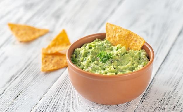 Schüssel guacamole mit tortillachips Premium Fotos