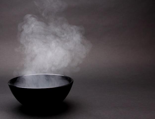 Schüssel heiße suppe auf schwarzem Premium Fotos