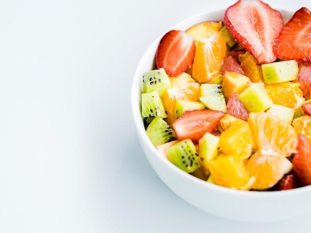 Schüssel heller salat der frischen frucht auf weißem hintergrund Kostenlose Fotos