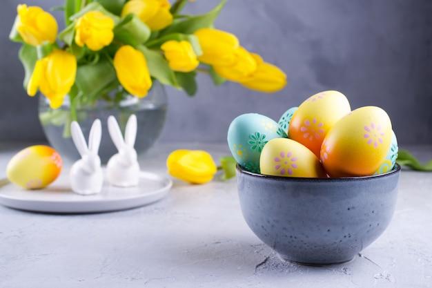 Schüssel mit bunten ostereiern; frühlings-osterndekoration auf grauem tisch mit strauß gelber tulpenblüten in glasvase; ostern innendekoration Premium Fotos