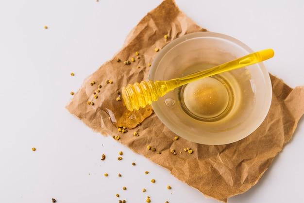 Schüssel mit honig schöpflöffel- und bienenpollen auf braunem papier Kostenlose Fotos