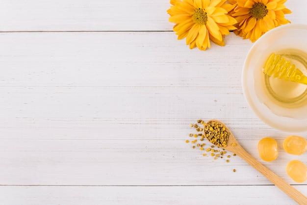 Schüssel mit honig süßigkeiten; bienenblütenstaub und -blumen auf hölzernem hintergrund Kostenlose Fotos