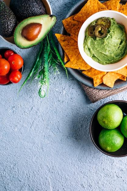 Schüssel mit mexikanischer guacamole auf vintage-holztisch, umgeben von tomaten, jalapeños-paprika, limetten und avocados. copyspace Premium Fotos