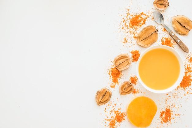 Schüssel mit orange flüssigkeit zwischen laub und pfeffer Kostenlose Fotos