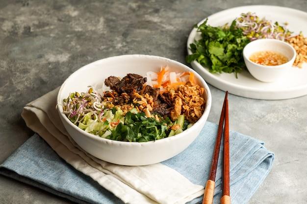 Schüssel mit traditionellem vietnamesischen nudelsalat - bun bo nam bo, mit rindfleisch, reisnudeln, frischen kräutern, eingelegtem gemüse und fischsauce Premium Fotos
