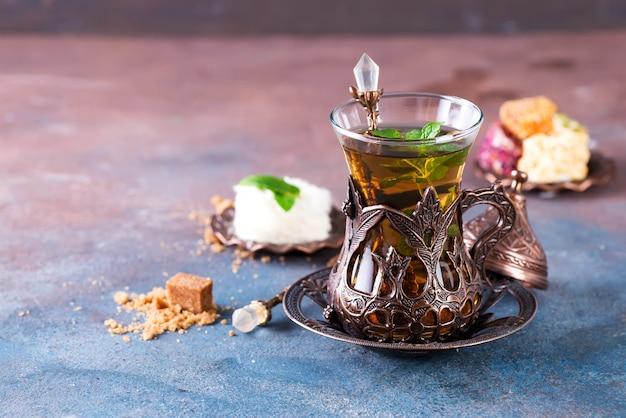 Schüssel mit türkischer zuckerwatte pismaniye und schwarzem tee mit minze Premium Fotos