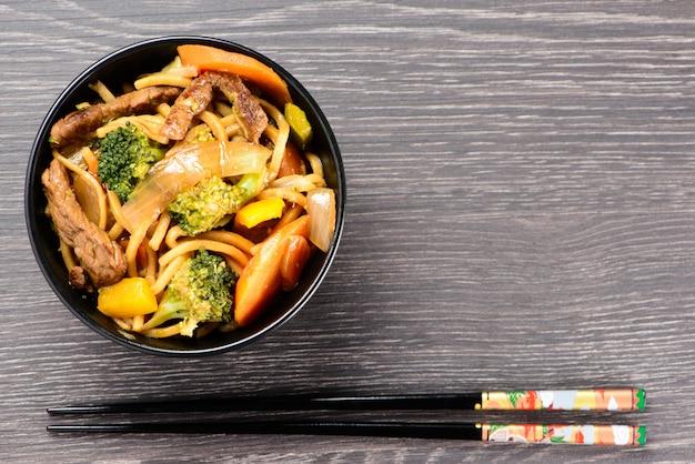 Schüssel mit yakisoba und hashi Premium Fotos