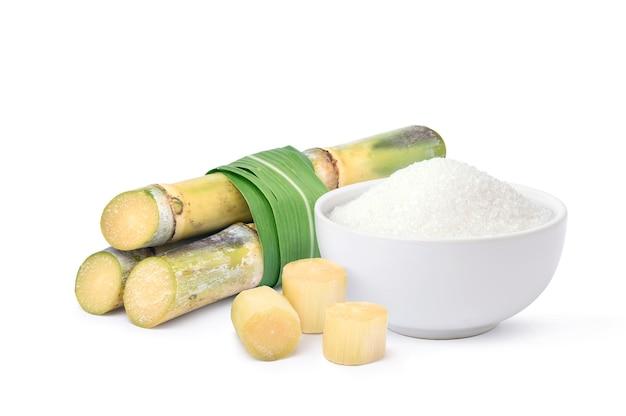 Schüssel mit zucker und zuckerrohr daneben Premium Fotos