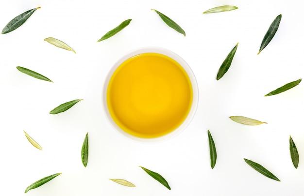 Schüssel natives olivenöl extra mit olivenblättern. zenitalflugzeug Premium Fotos