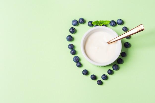 Schüssel natürlicher joghurt und neues blaubeerherz Premium Fotos