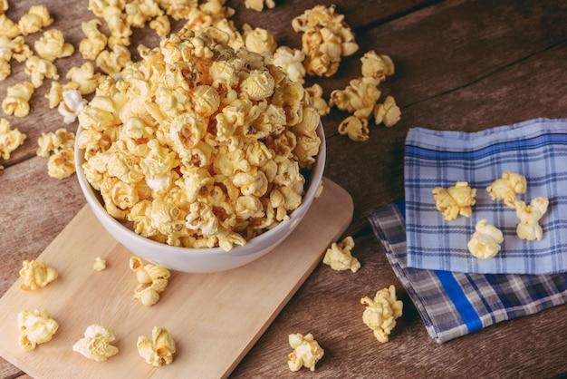 Schüssel popcorn auf dem holztisch, selektiver fokus Premium Fotos