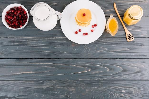 Schüssel rote johannisbeeren beeren; milch; honig und pfannkuchen auf hölzernen strukturierten hintergrund Kostenlose Fotos