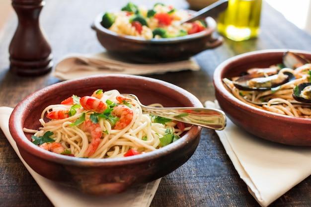 Schüssel spaghettis mit garnelen auf holztisch Kostenlose Fotos