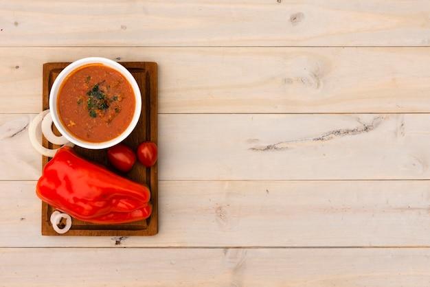 Schüssel tomatensauce und frische tomaten auf schneidebrett über holzoberfläche Kostenlose Fotos