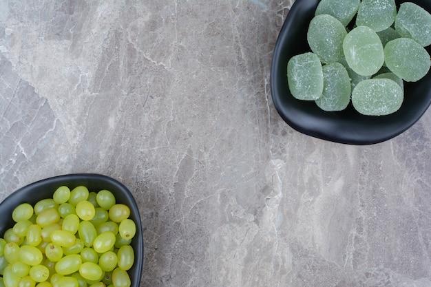 Schüssel trauben und marmeladenbonbons auf steinhintergrund. Kostenlose Fotos