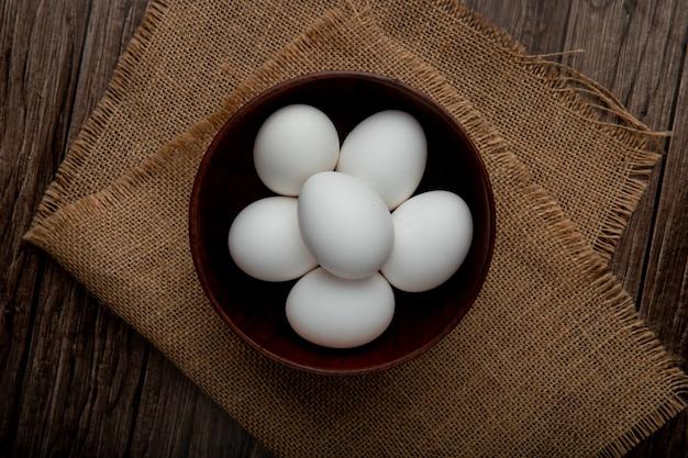 Schüssel voller eier auf sackleinenoberfläche und holztisch Kostenlose Fotos