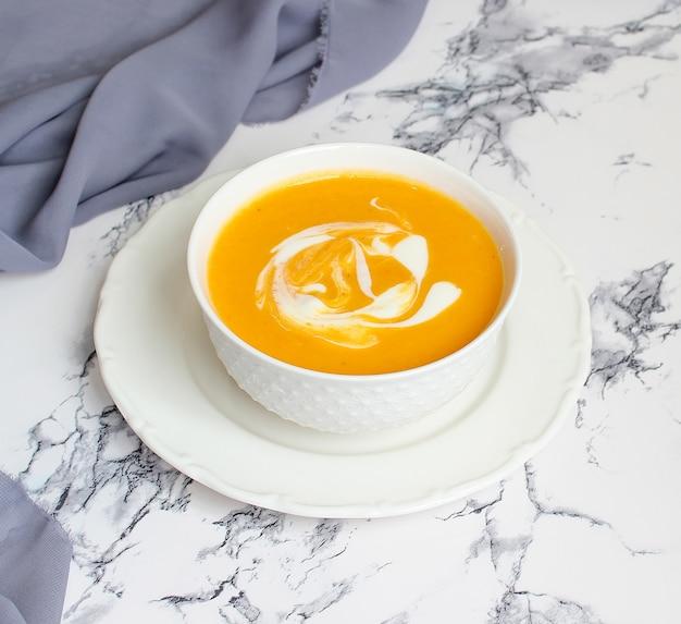 Schüsseln kürbissuppe auf weißem hintergrund mit grauem gewebe und scheiben des moschuskürbisses Premium Fotos