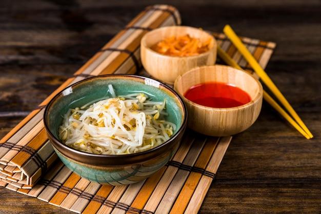 Schüsseln mit gekeimten bohnen und roter chili-sauce mit essstäbchen auf tischset über dem tisch Kostenlose Fotos