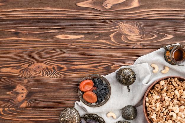 Schüsseln mit irdenen gemischten nüssen; teeglas und trockenfrüchte auf tischdecke über dem schreibtisch aus holz Kostenlose Fotos