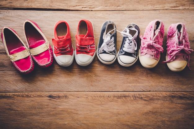 Schuhe für kinder auf holzboden Premium Fotos