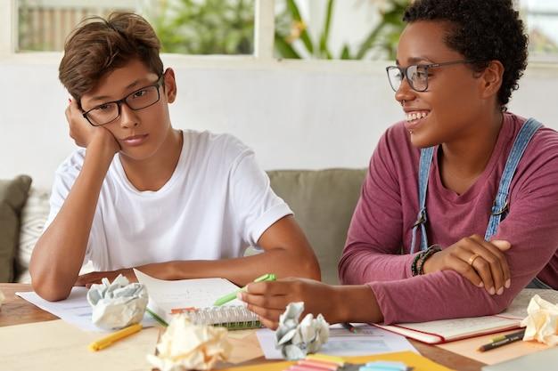 Schul- und bildungskonzept. erfreute erfahrene lehrerin hilft jugendlichen, mit der gruppe schritt zu halten, erklärt die grammatikregel und macht sich notizen im notizblock. teenager fühlt sich apathisch, weil er nicht lernen will Kostenlose Fotos