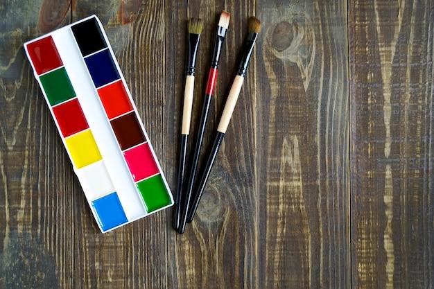 Schulaquarellzubehör und -bürsten für das malen auf einem dunklen hölzernen hintergrund mit kopienraum. ansicht von oben Premium Fotos