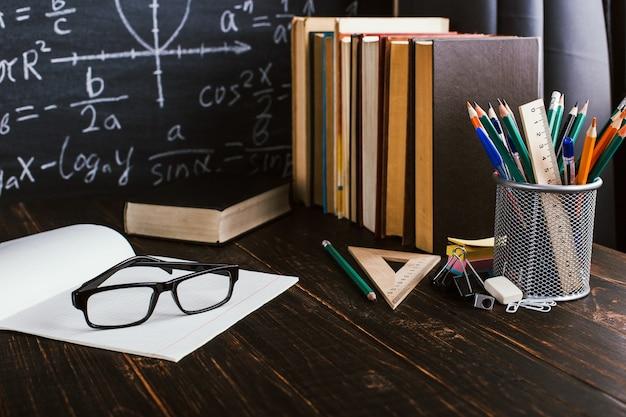 Schulbank im klassenzimmer, mit büchern auf hintergrund der tafel mit schriftlichen formeln Premium Fotos