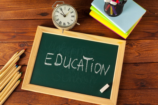 Schulbedarf auf einem holztisch und einer tafel Premium Fotos