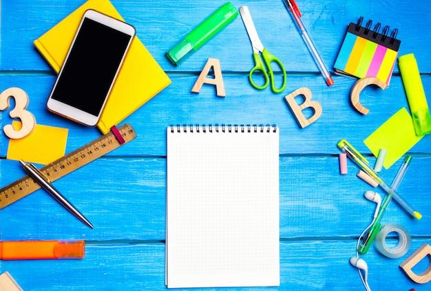 Schulbedarf in der schulbank, briefpapier, schulkonzept, blauer hintergrund, kreatives chaos Premium Fotos