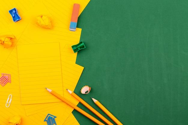 Schulbriefpapier und orange blatt papier liegen auf der grünen schulbehörde, die einen rahmen für text bildet. in der nähe von bleistift und zerknitterten seiten. kopieren sie platz wohnung legen draufsicht konzept bildung Premium Fotos